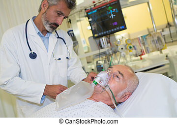 Doctor with patient wearing oxygen mask