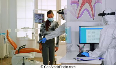 Doctor with protection suit inviting next patient in stomatology room for teeth examination during coronavirus. Assistant and dentist medic wearing overall, face shield, mask, gloves in dental clinic