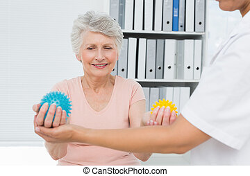Doctor with senior patient using stress buster balls -...
