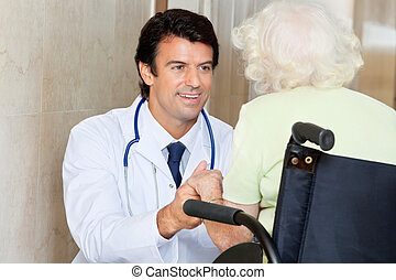 Doctor With Senior Woman In Wheel Chair