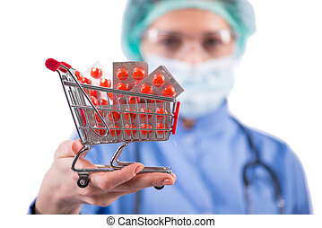 Doctor with shopping cart full of pills isolated on white