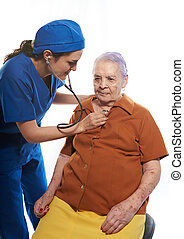 Doctor with stethoscope checking old woman