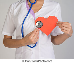 Doctor with stethoscope examines red paper heart