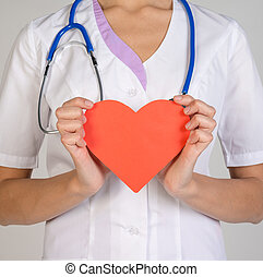 Doctor with stethoscope holding red paper heart