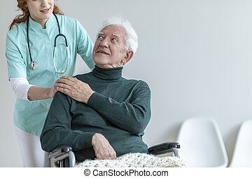 Doctor with stethoscope supporting disabled senior man in the wheelchair in a hospital