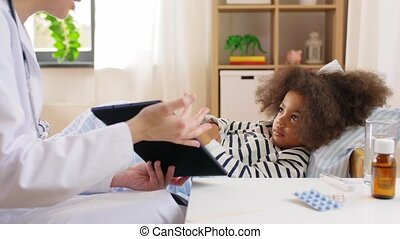 doctor with tablet computer and sick girl in bed