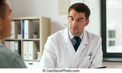 doctor with tablet pc and male patient at hospital -...