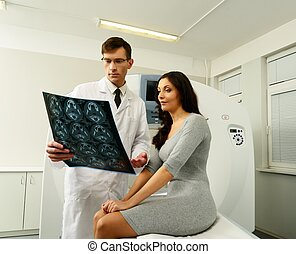 Doctor with young woman patient looking at the computed tomography results