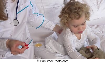 doctor woman giving child patient remedy with spoon sitting...