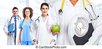 Doctor woman hands with scales and apple.