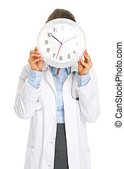 Doctor woman holding clock in front of face
