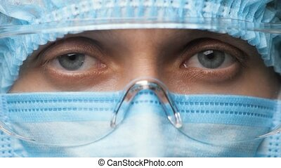 Eyes Woman Doctor or Healthcare Worker in Personal Protective Kit Looking at Camera. Nurse Wearing Safety Uniform and Protective Glasses during Novel Coronavirus 2019-nCoV, Pandemic Covid-19. Close Up
