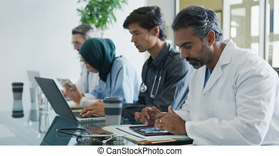 Doctor working with colleagues at table smiles to camera 4k