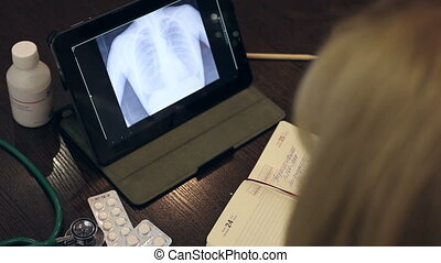Doctor working with tablet computer and documents