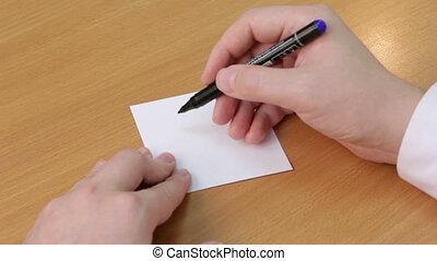 Doctor writes stsatus alive - Doctor's hand closeup