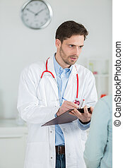 doctor writing a medical prescription in hospital room