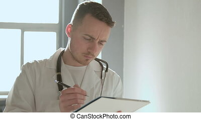 Doctor writing on a clipboard in the hospital