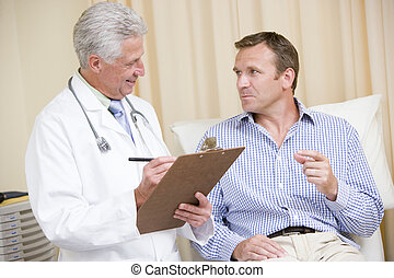 Doctor writing on clipboard while giving man checkup in exam...