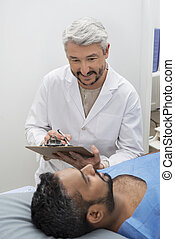 Doctor Writing On Clipboard While Looking At Patient On Bed