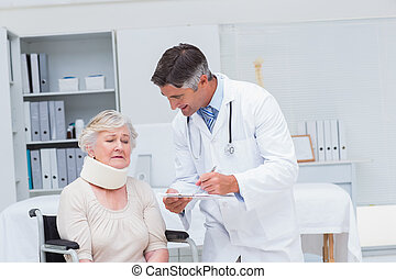 Doctor writing prescription for patient wearing neck brace