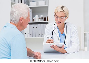 Doctor writing prescription for senior man