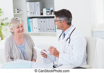 Doctor writing prescriptions for senior female patient