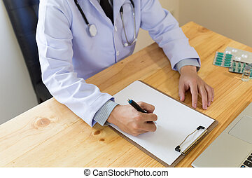 doctor writing RX prescription in medical office clinic with drugs on desk