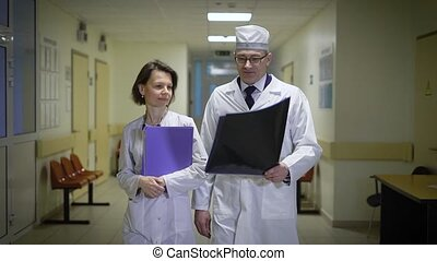 Doctors, a man and a woman go on a hospital corridor and communicate with each other. Medical workers keep a folder with the history of patients, and X-rays.