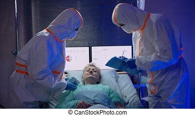 Doctors and infected patient in hospital, coronavirus concept.