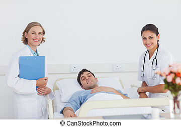 Doctors and patient looking at the camera