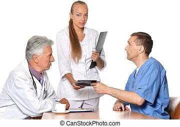 Doctors at table exemining xray