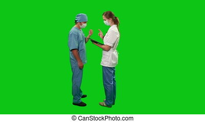 A nurse reports the patient's state to the surgeon, they walk together into the frame then turn right.