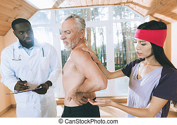 Doctors examine an elderly man who has a backache in his back.