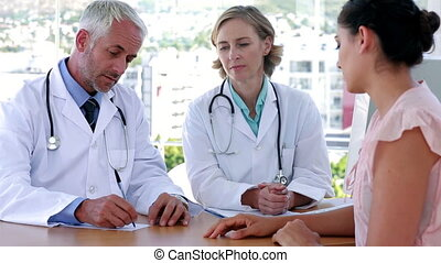 Doctors explaining something to patient sitting at desk in...