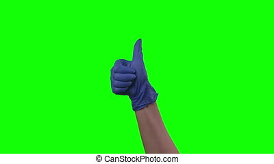 Doctors female hand in blue glove is holding thumb up making gestures like. Green screen. Gestures chroma key pack. Footage for ads. Close up motion.