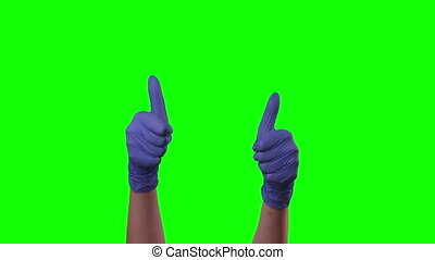 Doctors female hands in blue glove is holding thumb up making gestures like. Green screen. Gestures chroma key pack. Footage for ads. Close up motion.
