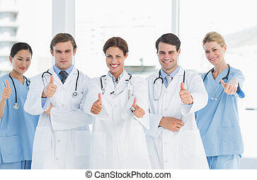 Doctors gesturing thumbs up at hosp