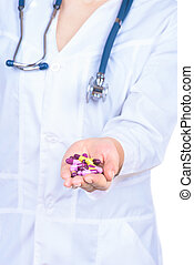 Doctor's hand holding many yellow tablets