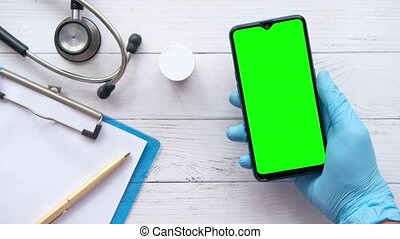 doctor's hand in protective gloves using a smartphone.