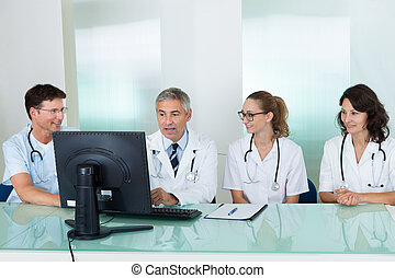 Doctors having a meeting seated at a table in front of a...