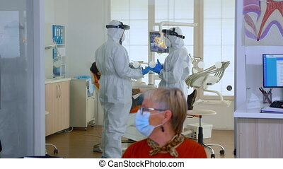 Doctors in full virus protection uniform talking in surgery room