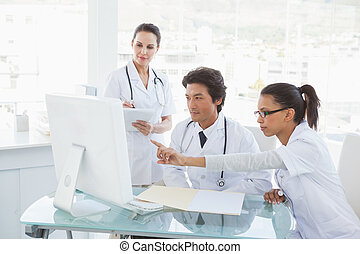 Doctors looking at the computer monitor