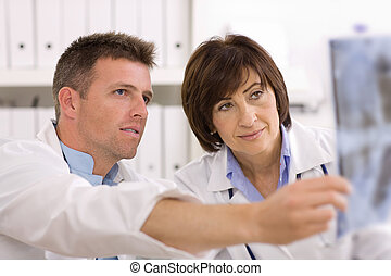 Doctors looking at x-ray image - Doctors coworking looking...