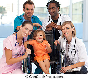 Doctors playing with a baby in a wheelchair