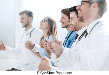 doctors sit in a row and hold hands of each other