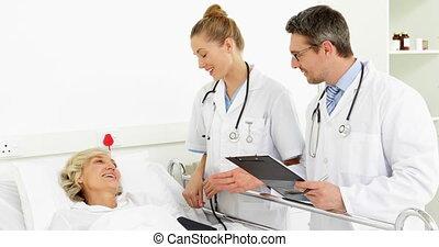Doctors speaking with sick patient