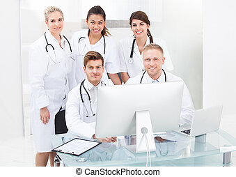 Team of doctors using desktop PC together at desk in clinic