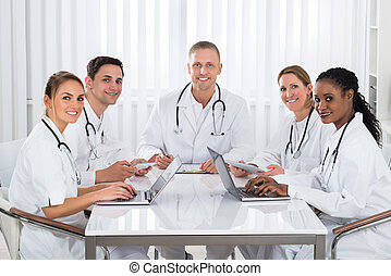 Doctors With Digital Tablet And Laptop At The Meeting