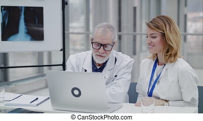 Doctors with laptop at the desk discussing issues. Slow ...