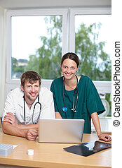 Doctors With Laptop Leaning On Desk